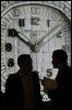 Deux personnes devant un écran géant au salon du luxe et de l'horlogerie Baselworld, le 25 mars 2009 (© AFP - Fabrice Coffrini)