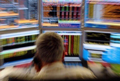 Un trader devant des écrans surveille l'évolution des marchés (©  - Eric Piermont)