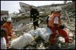 Des secouristes portent les corps de victimes du bombardement israélien à Qana, le 30 juillet 2006 (© AFP - Nicolas Asfouri)